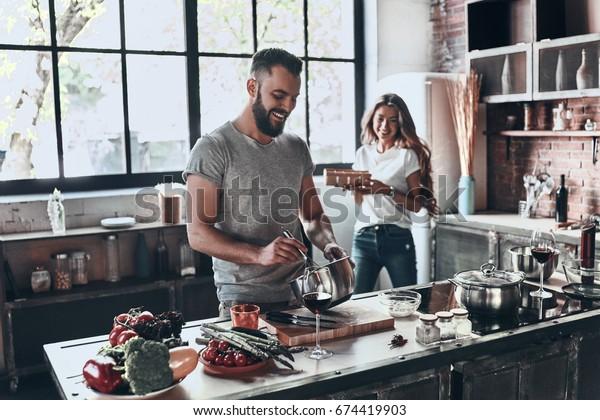 秘密の材料は愛。家で過ごしながら、一緒に健康的な食事を準備する美しい若い夫婦