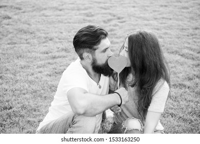 Secret kiss. Man bearded hipster and pretty woman in love. Summer vacation. Happy together. Couple in love cheerful youth booth props. Emotional couple radiating happiness. Couple relaxing green lawn.