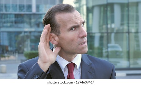 Secret, Middle Aged Businessman Listening with Attention