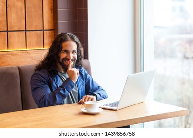 Secret! Portrait of happy handsome intelligence young adult man freelancer in casual style sitting in cafe with laptop and showing shh sign, finger holding near lips. Indoor, lifestyle concept