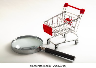 Secret shopper or mystery shopper concept with a magnifying glass and a shopping basket or trolley isolated on a white background and copy space