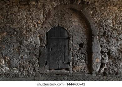 secret wooden door in the wall of an ancient castle