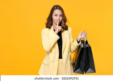 Secret young woman in suit jacket hold package bags with purchases after shopping say hush be quiet with finger on lips shhh gesture isolated on yellow background studio portrait. Black friday sale