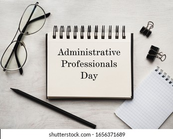 Secretaries Day and Admin Day. Greeting card. Close-up, view from above, wooden surface. Concept of preparation for a professional holiday. Congratulations for relatives, friends and colleagues.