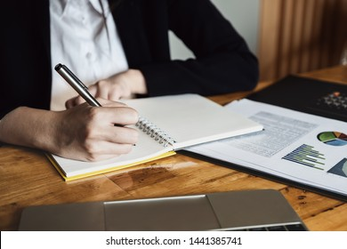 Secretary or company employee Hold the pen to take notes on the notebook in the meeting with using budget data document and laptop computer to analyzing data.