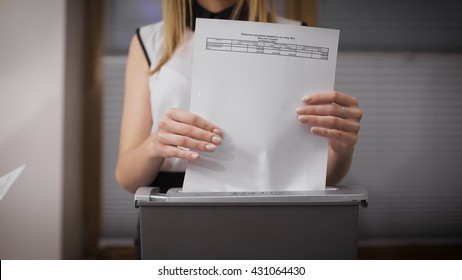 Secretary destroys documents using a special apparatus. Hiding confidential financial information. Close-up on the girl's hands