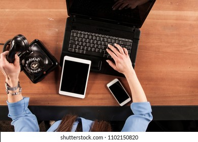 secretary dials a phone number and writes on the keyboard at the same time, top view