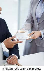 Secretary giving cup of fresh coffee to her chief