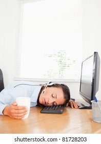 A secretary with a headset and a cup of coffee sleeps in an office