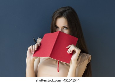 The secretary hides her face in a notebook on a blue background. Business woman