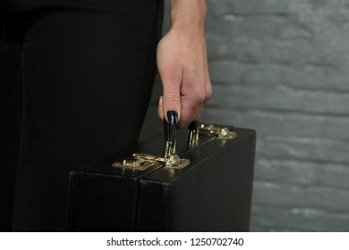 secretary holds a briefcase in his hand