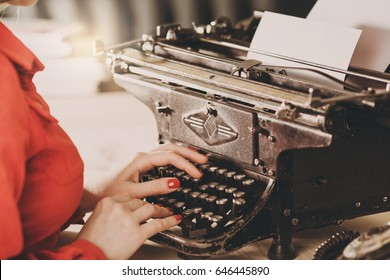 Secretary at old typewriter with telephone. Young woman using typewriter. Business concepts. Retro picture style.