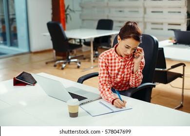 Secretary on phone writing a note