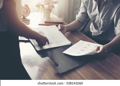 secretary showing document to her boss in the office