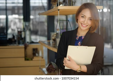 Secretary woman holding a document file and smile on face.