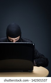 Secretive computer hacker bent closely over a computer screen in the darkness stealing important and private information, conceptual image