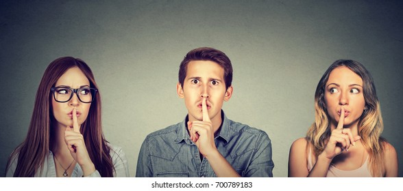 Secretive people man and two women with finger to lips gesture