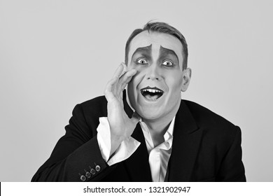 Secretly between you and me. Performance art and pantomime. Actor acting secret. Mime artist. Mime with face paint. Man with mime makeup. Theatre actor miming. Comedian or tragedian performer.