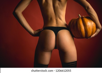Secrets of Magic for Happy Halloween. Female with sexy ass posing on pumpkin. Sexy Models Posing In Lingerie on halloween background. The Most Popular Candy for Halloween. Halloween sexy concept
