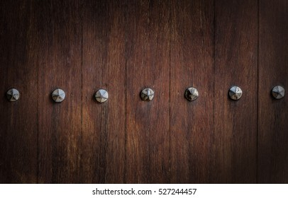 Section of ancient wooden door with  rusty metal nail heads