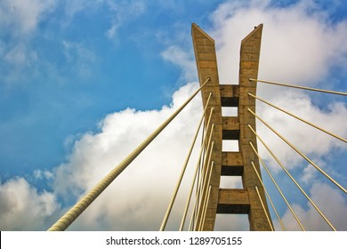 Section of a cable-stayed bridge against a vibrant blue sky with white clouds