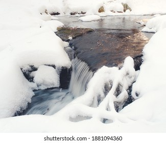 A section of cascades on a freezing river after a snowfall in the early winter