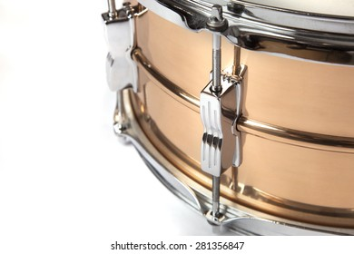 Section of a copper snare drum against a white background.