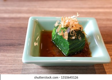 A section of cut blanch spinach with bonito flake decoration and soy sauce