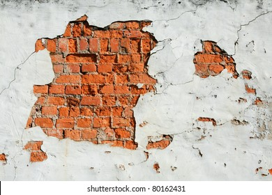 A section of damaged wall exposing the red bricks underneath
