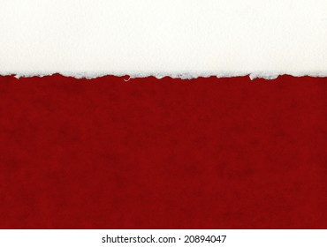 A section of deckled edge paper on a red background.