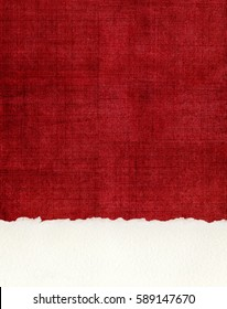 A section of deckled edge paper on a textured, red cloth background.