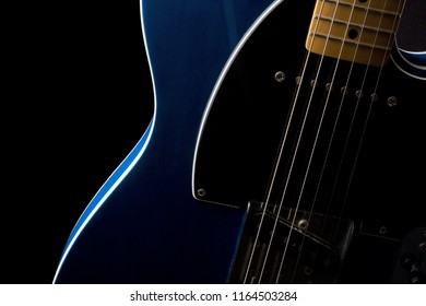 Section of an electric guitar body and neck in close-up with strong side light