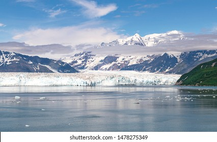 a section of the face of the hubbard glacier in yakutat bay in alaska with the st elias mountains and beautiful clouds in a blue sky in the background