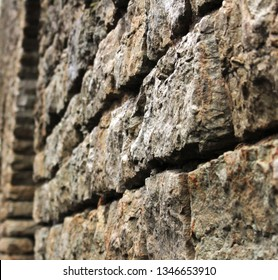 The section of the massive fortification wall of an ancient castle in Europe is the impenetrable walls of bastions close up at an angle. The fortification built during the time of the Knights remains