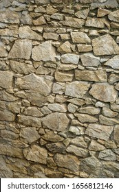 Section of an old granite stone wall with failing mortar and no pointing.