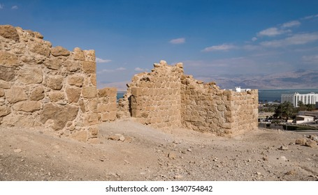 a section of a partially reconstructed ancient roman fortress sits above the dead sea resort town of ein bokek with the moav mountains of jordan in the background