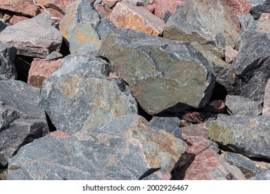 Section of placer of stones gray and red granite different sizes outdoors in summer day