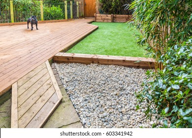 A section of a residential garden, yard with wooden decking, patio over a fish pond, a section of artificial grass and an area of stone pebble. There is a bamboo plant and a dog in the garden.