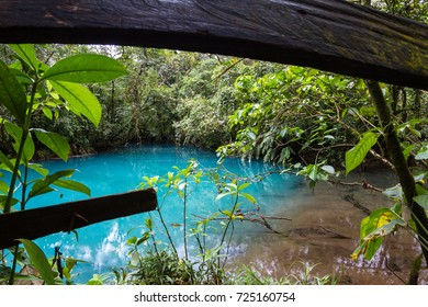 Section of the river where brown meets turquoise viewed thru the fence