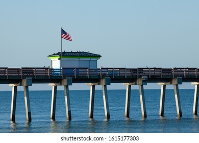 A section of the Venice (FL) municipal fishing pier is shown highlighting the bait shop. An American flag is waving in the breeze and several pigeons are on the roof of the bait shop.