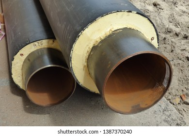 sections of two black water pipes in the insulation and winding