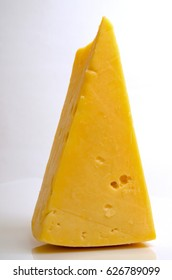 Sector of hard cheese on a light background close-up.