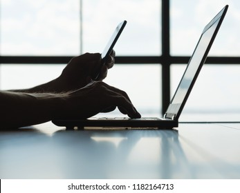 secure online payments. two factor authorization. man hands holding mobile phone and entering password message on laptop.