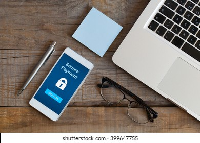 Secure payment notification in a mobile phone screen. Smart phone on a wooden desk at the office.