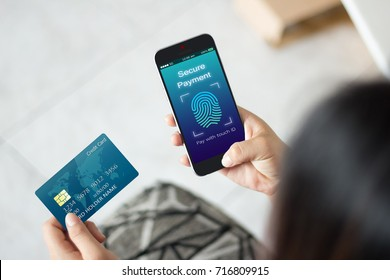 Secure payment with touch id scan concept.Woman hands using mobile phone and holding credit card