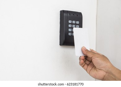 Security alarm keypad with female hand and card, closeup
