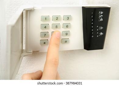 Security alarm keypad with male hand, closeup