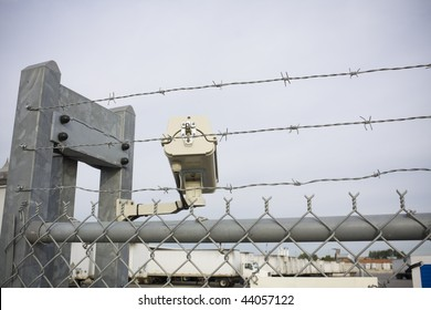 Security cam overlooking truck yard with chain-link fence and barbed wire