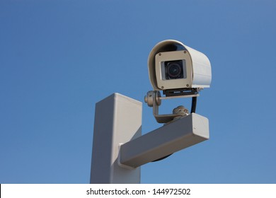 Security camera facing left before the background of a clear blue sky.