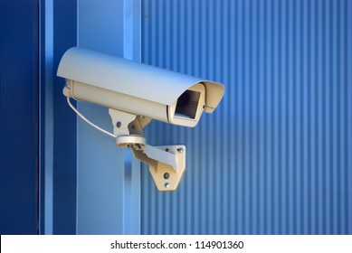 Security camera on the blue wall.